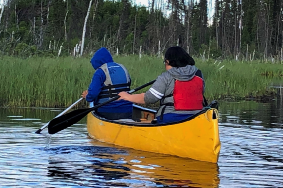 Grandmother's Bay youth paddling through a wetland area.